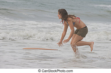 Athletic teen girl throwing a skimboard - Athletic teen girl...
