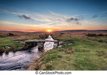 Dartmoor Bridge - A granite clapper bridge at sunset on...