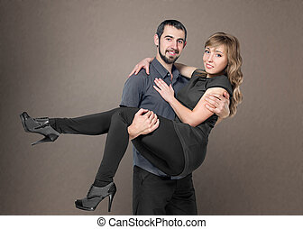 young men holding woman in arms posing in studio