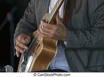 Playing Acoustic Slide Guitar - Selective focus on the hands...