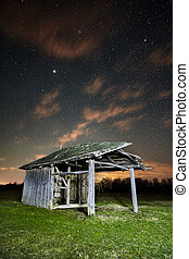Shack on a meadow at night - Night landscape with a shed on...