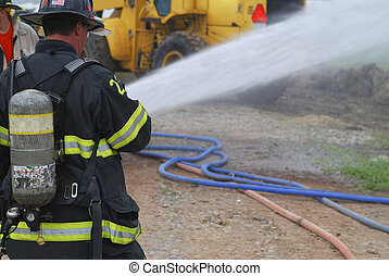 Fire fighter at a barn fire sprays water on the fire.