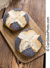Fresh baked Pretzel Roll (with Poppyseed) on rustic wooden...