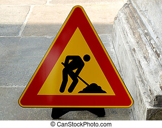 Road work sign on a sidewalk pavement