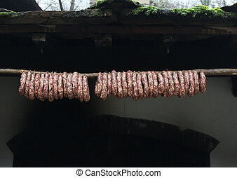 Raw sausages hang outdoor