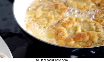 Frying pork meat coated with breadcrumbs in a pan