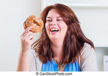 Plump and happy woman eating donuts at the table - Plump and...