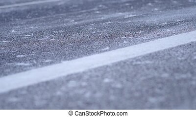 Falling snow on roadway - Close up of fresh snow falling to...