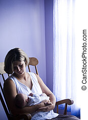 Mother rocking newborn baby in rocking chair next to window...
