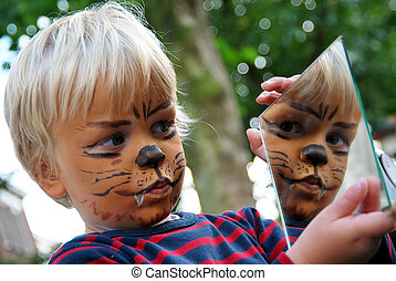 make-up lion - Young boy admiring his painted face in a...