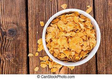 Cornflakes - Portion of golden Cornflakes on wooden...