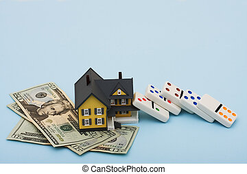 Housing Market - A model house with fallen dominoes sitting...