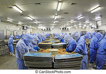 Workers in a meat processing production line, in a food...