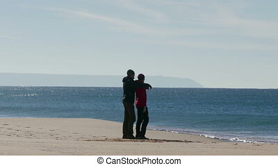 Happy Middle-aged Couple Walking on Beach - Happy...