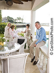 Family on vacation relaxing on terrace - Portrait of family...