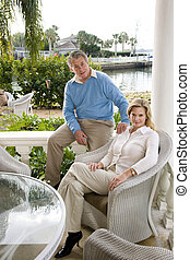 Mature couple relaxing on waterfront terrace - Portrait of...