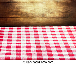 Checkered red tablecloth over wooden background