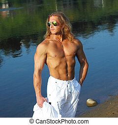Beautiful long-haired man with a naked muscular torso walks on the beach. Fitness model man in sunglasses on the beach near the water.