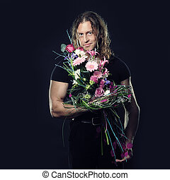 manly muscular man with long hair holds in hands a bouquet...
