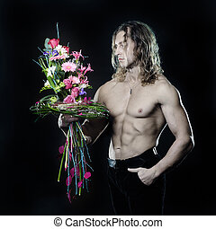 The long-haired male fitness model shirtless holding a...