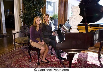 Piano lesson - Portrait of mother and teen daughter sitting...