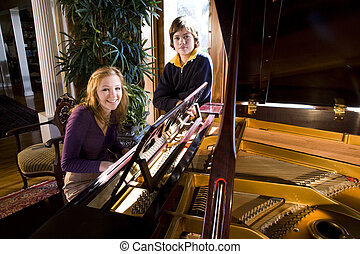 Piano practice - Teenage girl playing piano while younger...