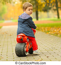 cute little biker on road with motorcycle Young boy on toy...
