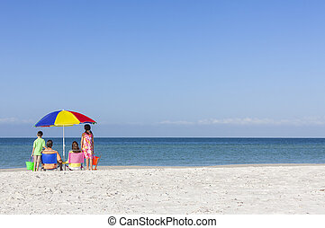 Family Alone on Beach With Umbrella - Rear view of a happy...