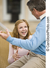 Father and teenage daughter conversing - Father and teenage...