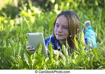 Pretty young girl lying in the grass at park with a tablet.