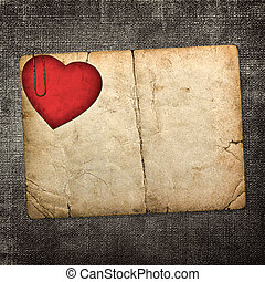 old paperboard card with red paper heart on a dark fabric...