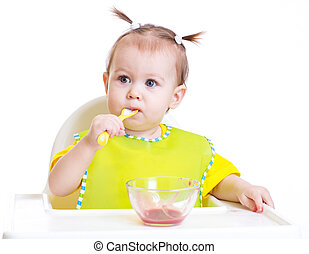 Baby eating with spoon sitting at table isolated