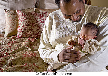 Father holding newborn baby - Father holding week-old...