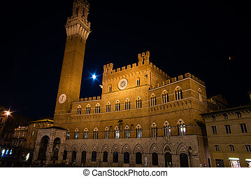 Siena town hall with moon at background - Night scene in...