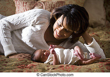 Mother and newborn - African American mother admiring her...