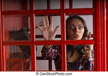 Terrified woman trapped in a telephone booth staring out...