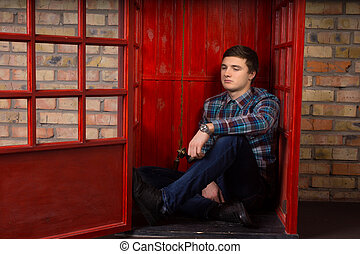 Bored young man waiting for a phone call on a public pay...