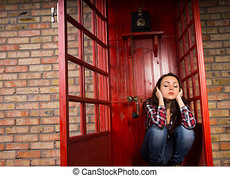 Upset woman sitting blocking her ears in a telephone booth...