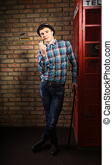 Dapper English gentleman leaning on a phone booth - Dapper...