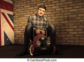 Happy Young Man Sitting on Vintage Toy Car - Happy Handsome...