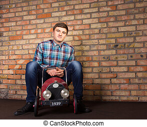 Young Man Sitting on Vintage Toy Vehicle - Young Handsome...