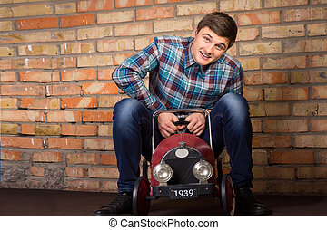 Young man having fun riding a toy truck - Playful handsome...