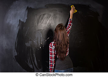 Young teacher or student cleaning the blackboard