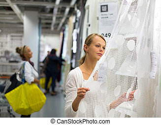 Pretty, young woman choosing the right curtains for her...