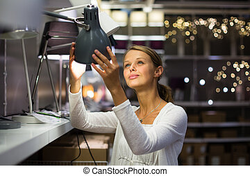 Pretty, young woman choosing the right lamp for her...