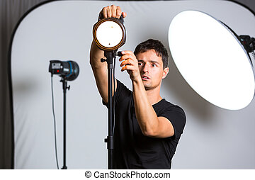 Young pro photographer in his studio setting up lights for...
