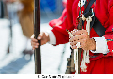 Hands of a musketeer holding a musekt and slow match or...