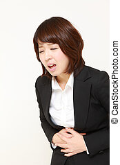 stomachache - studio shot of young Japanese businesswoman on...