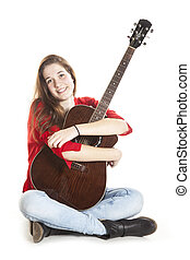 teenage holds arms around guitar in studio - teenage girl...