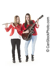 two teenage sisters play flute and guitar in studio with...